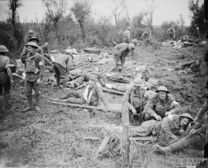 THE BATTLE OF PASSCHENDAELE, JULY-NOVEMBER 1917 Battle of Pilckem Ridge. Wounded men are tended by medical staff as they lie on stretchers on the grass at an RAMC advanced dressing station near Boesinghe (on the left flank of the British Fifth Army). One man has his arm in a sling. 31 July 1917 Battle of Pilckem Ridge. Wounded men are tended by medical staff as they lie on stretchers on the grass at an RAMC advanced dressing station near Boesinghe (on the left flank of the British Fifth Army). One man has his arm in a sling. 31 July 1917. © IWM (Q 5730)